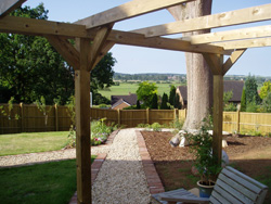 A photo after with new planting scheme, fence, pergola, deck and paths